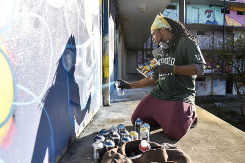 "Brandan Odums spray-paints a wall for ""Exhibit Be"" in 2014."