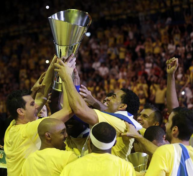 Maccabi of Tel Aviv captain Maccabi Guy Pnini, right, and his teammate Maccabi Tel Aviv's Alex Tyus hold the trophy as they celebrate with teammates after winning the Euroleague Final Four final against Real Madrid in Milan, Italy, Sunday, May 18, 2014. (AP Photo/Luca Bruno)