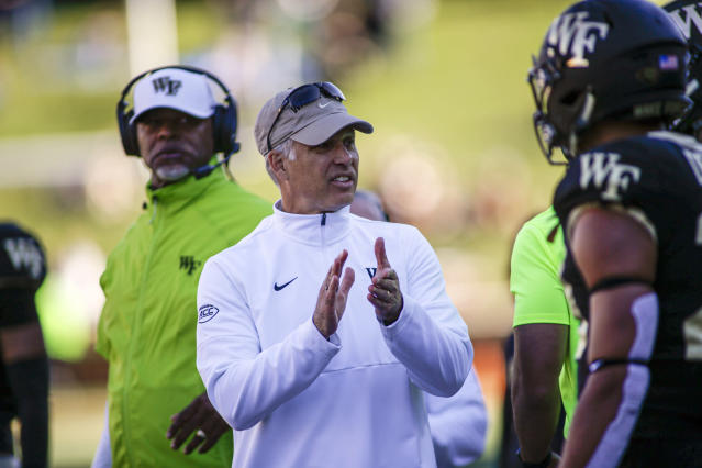 Wake Forest head coach Dave Clawson, center, talks to his team as they play North Carolina State in the second half of an NCAA college football game in Winston-Salem, N.C., Saturday, Nov. 2, 2019. Wake Forest won 44-10. (AP Photo/Nell Redmond)