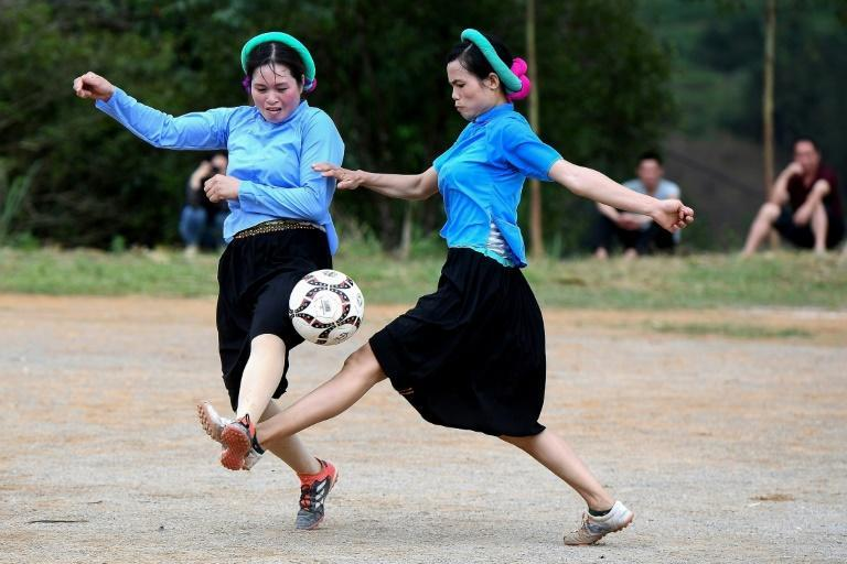 Ethnic San Chi women dressed in traditional costumes play a friendly football match as part of the Soong Co festival celebrations in northern Vietnam's Quang Ninh province