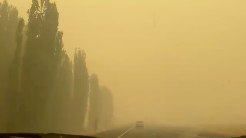 A vehicle is engulfed in yellowish smoke during bushfires near Cooma