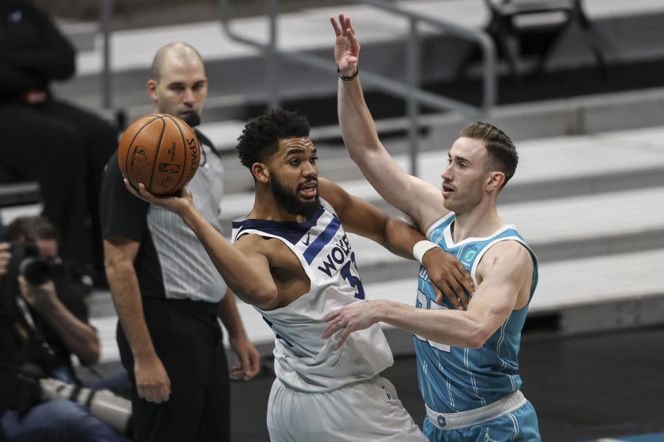 Minnesota Timberwolves center Karl-Anthony Towns, left, passes the ball as Charlotte Hornets forward Gordon Hayward (20) defends during the second half of an NBA basketball game in Charlotte, N.C., Friday, Feb. 12, 2021. (AP Photo/Nell Redmond)