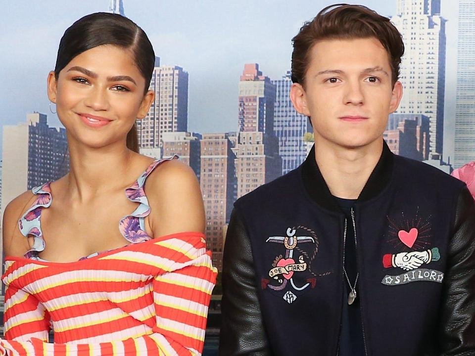 """Zendaya, Tom Holland, and Laura Harrier sitting on a bench together while promoting """"Spider-Man: Homecoming."""""""