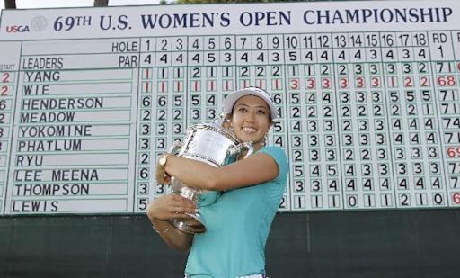 Michelle Wie pass with the trophy after winning the U.S. Women's Open golf tournament in Pinehurst, N.C., Sunday, June 22, 2014. (AP Photo/Bob Leverone)