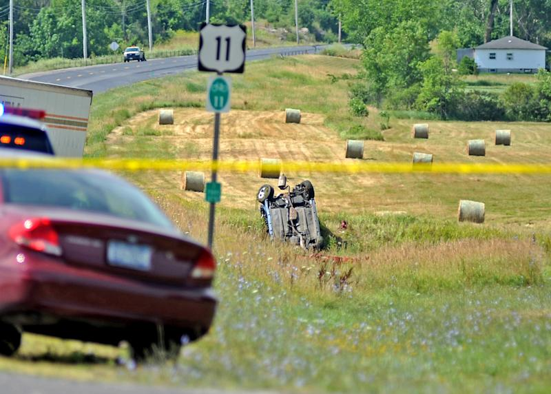 An overturned vehicle lies in field at the scene of a fiery chain-reaction crash in a roadwork zone on Route 11 Thursday, July 19, 2012 in Antwerp, N.Y. Police say a tractor-trailer driven by James A. Mills Jr. of Myerstown, Pa., struck several vehicles that had slowed or stopped on the road. Five died in one SUV. They're identified as 42-year-old Laurie Dana of Lawrence; her daughters, 14-year-old Catelyn and 11-year-old Lauren; 69-year-old Janet Dana; and 14-year-old Shannon Planty. Police say another driver, 59-year-old Maryann Gregory of Dickinson Center, died at a hospital. (AP Photo/The Watertown Daily Times, Amanda Morrison) SYRACUSE OUT
