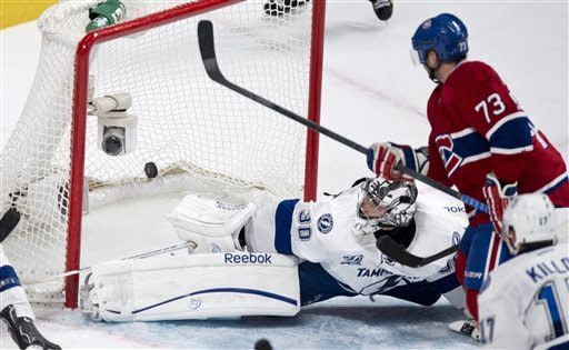 The puck sails into the net past Tampa Bay Lightning goalie Ben Bishop on a power-play goal by Montreal Canadiens' Brian Gionta, not shown, as Canadiens' Michael Ryder watches during the third period of their NHL hockey game, Thursday, April 18, 2013, in Montreal. The Canadiens won 3-2. (AP Photo/The Canadian Press, Paul Chiasson)