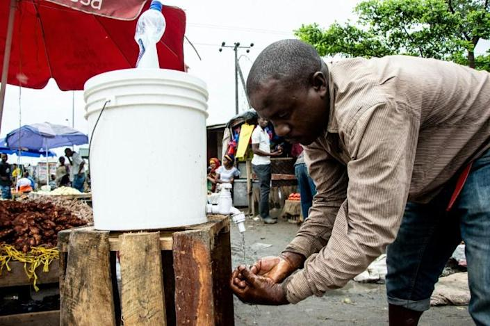 A man washes his hands with chlorinated water at Mabibo market in Dar es Salaam (AFP Photo/Ericky BONIPHACE)