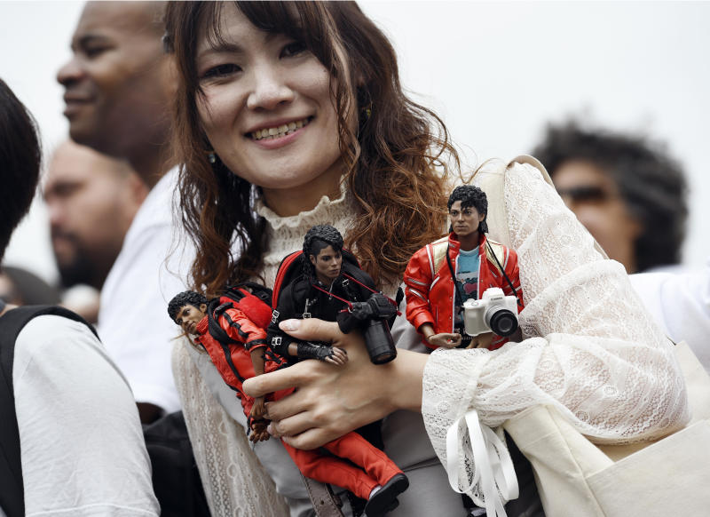 Yasuyo Kaneko of Japan holds Michael Jackson action figures outside the late pop star's final resting place in Holly Terrace at Forest Lawn Cemetery, Tuesday, June 25, 2019, in Glendale, Calif. Tuesday marks the 10th anniversary of Jackson's death. (Photo by Chris Pizzello/Invision/AP)