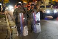 CORRECTS TO JOHN CHISHOLM NOT JOHN CHISOLM - National Guardsmen in riot gear stand in the street Friday, Oct. 9, 2020, in Wauwatosa, Wis. On Wednesday, District Attorney John Chisholm refused to issue charges against Wauwatosa Police Officer Joseph Mensah for the Feb. 2 fatal shooting of 17-year-old Alvin Cole at Mayfair Mall. (AP Photo/Morry Gash)