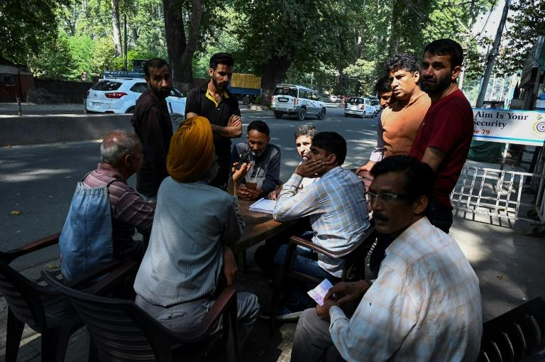 People gather to make calls on September 3, 2019, at a makeshift phone booth set up by Indian security forces during a lockdown in Srinagar, before India's government said it was easing a phone blockade of Kashmir