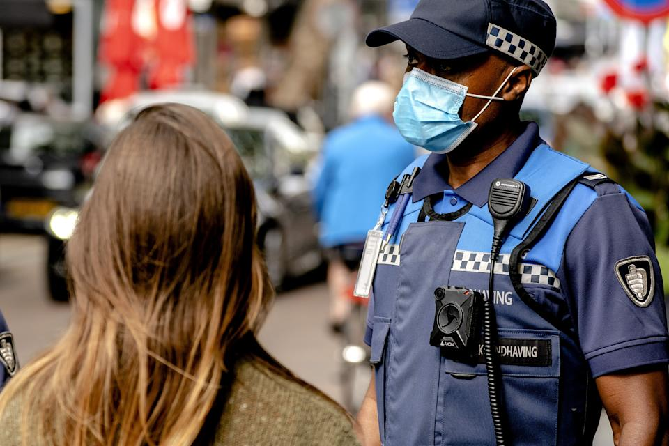 A Dutch police officer wears a nose and face mask as the municipality of Rotterdam  enforces the mandatory wearing of mask in large parts of the city to curb the spread of the coronavirus on August 23, 2020. (Photo by Sander KONING / ANP / AFP) / Netherlands OUT (Photo by SANDER KONING/ANP/AFP via Getty Images)