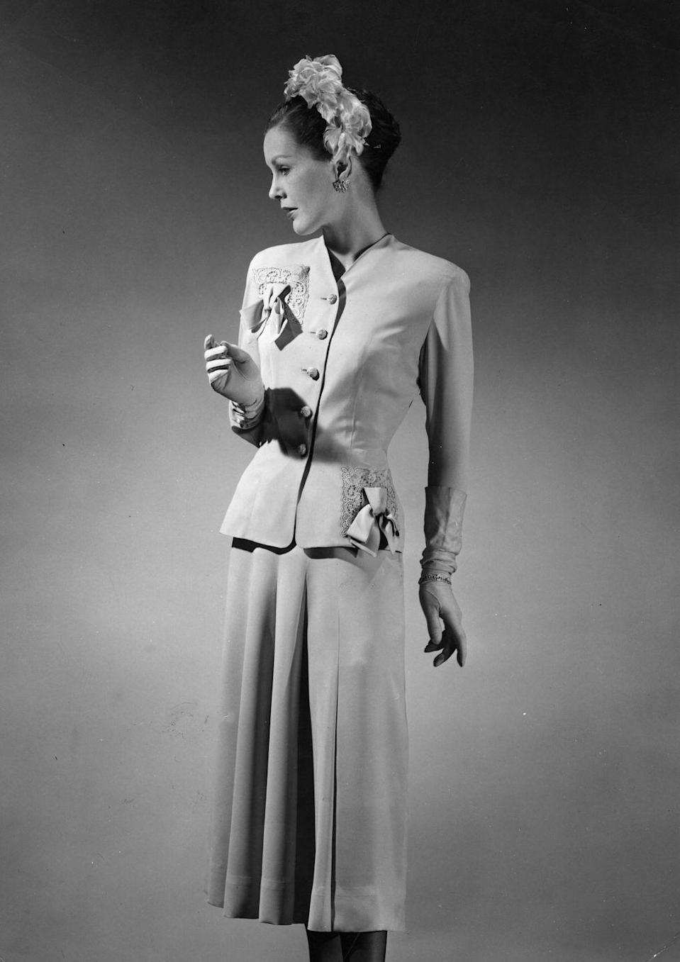 <p>A model shows a fitted two-piece suit, wearing gloves and decorated headband.</p>