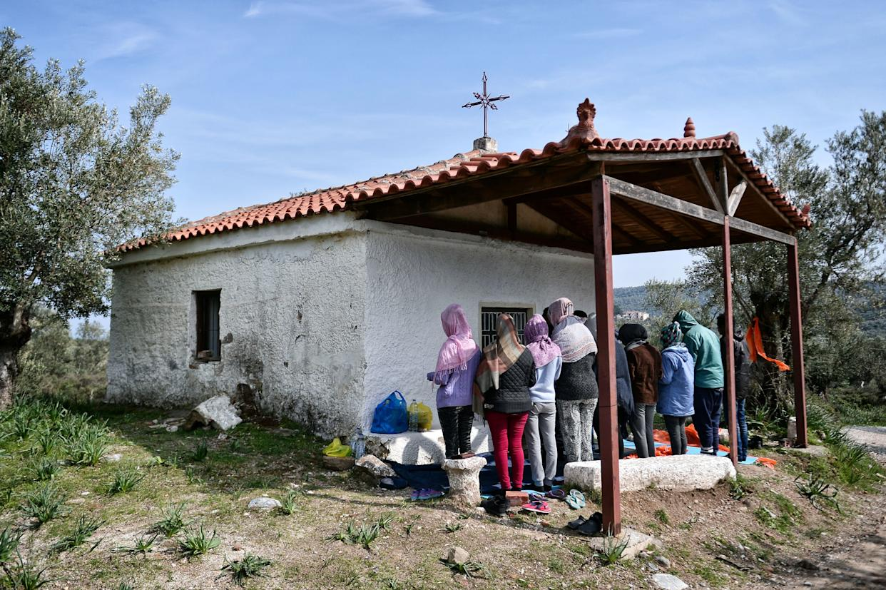 A picture taken on March 16, 2017 shows African Christian migrants praying at a hill church near the Moria migrant camp on the island of Lesbos, Greece. (Photo: LOUISA GOULIAMAKI via Getty Images)