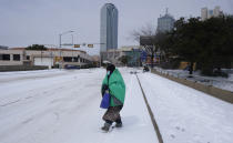 A woman wrapped in a blanket crosses the street near downtown Dallas, Tuesday, Feb. 16, 2021. Temperatures dropped into the single digits as snow shut down air travel and grocery stores. (AP Photo/LM Otero)