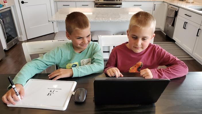 Jack Hartman, left, and his brother, Luke, work on their laptop for their virtual learning lessons this spring in Oak Creek, Wis.