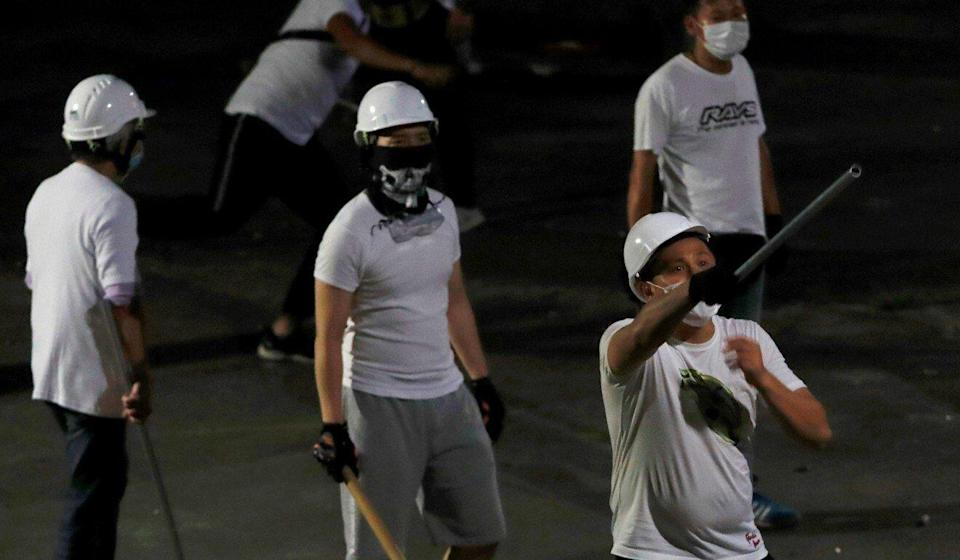 Men in white T-shirts with poles seen in Yuen Long that night. Photo: Reuters