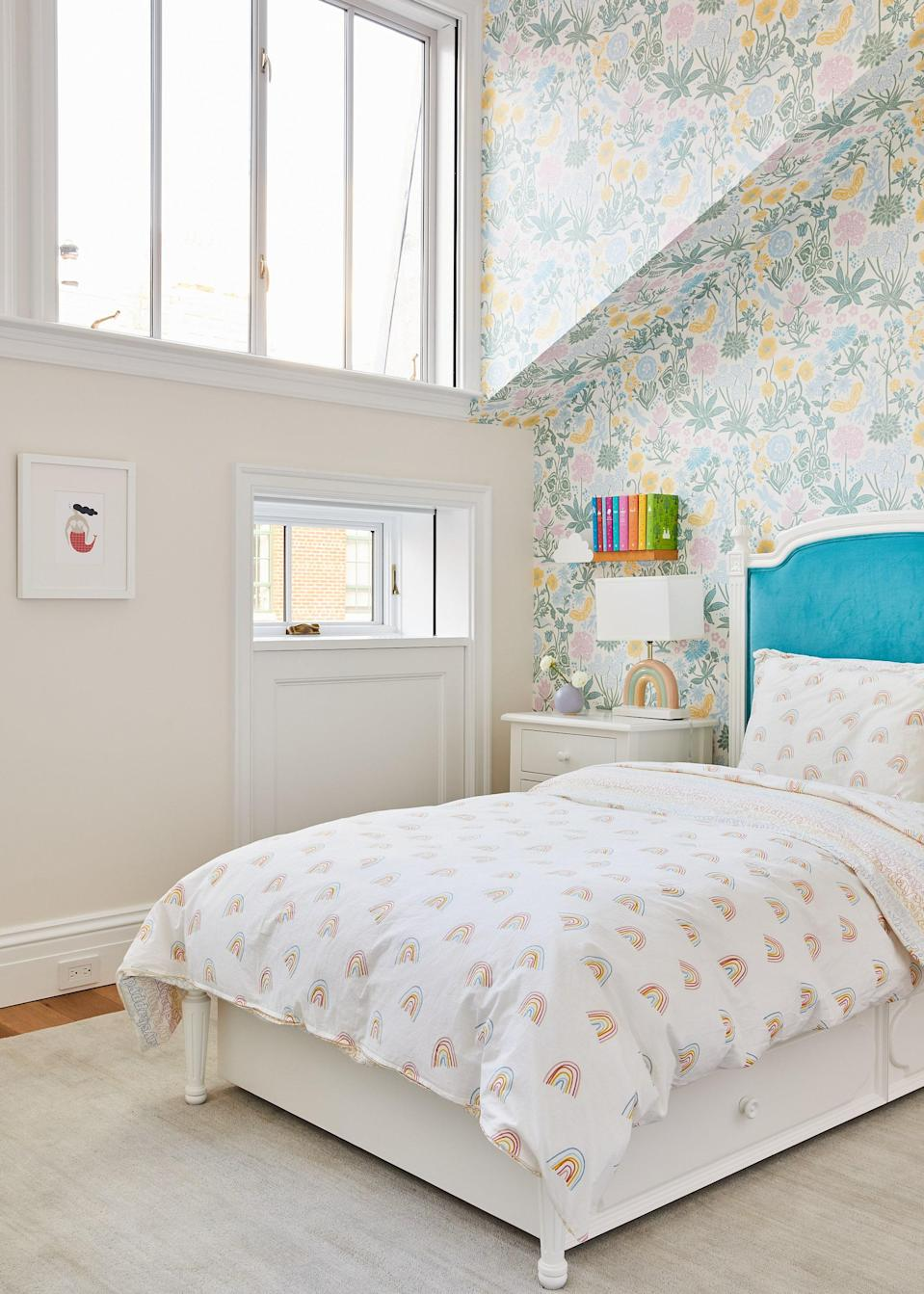 Floral Sandberg wallpaper and a vibrant blue on the Beautiful Bed Co. headboard strike a playful note in the daughter's room.