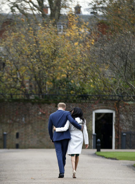 "FILE - In this Monday Nov. 27, 2017 file photo Britain's Prince Harry and Meghan Markle walk away after posing for the media in the grounds of Kensington Palace in London. In a stunning declaration, Britain's Prince Harry and his wife, Meghan, said they are planning ""to step back"" as senior members of the royal family and ""work to become financially independent."" A statement issued by the couple Wednesday, Jan. 8, 2020 also said they intend to ""balance"" their time between the U.K. and North America. (AP Photo/Alastair Grant, File)"
