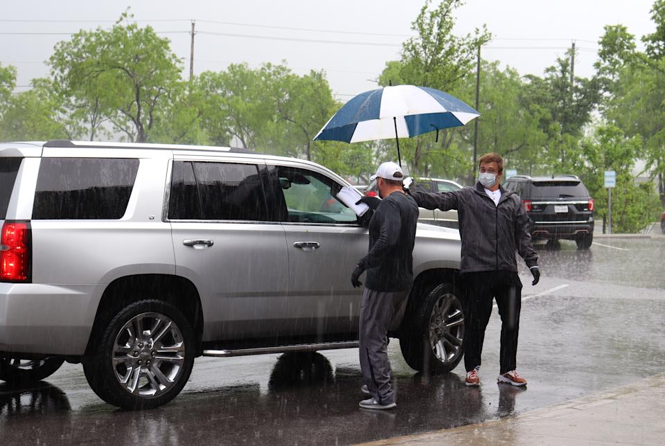 Texas quarterback Sam Ehlinger holds up an umbrella for coach Tom Herman as he hands out school curriculum to a family at an Austin-area Boys & Girls club. (Photos courtesy Boys & Girls Club of the Austin Area)