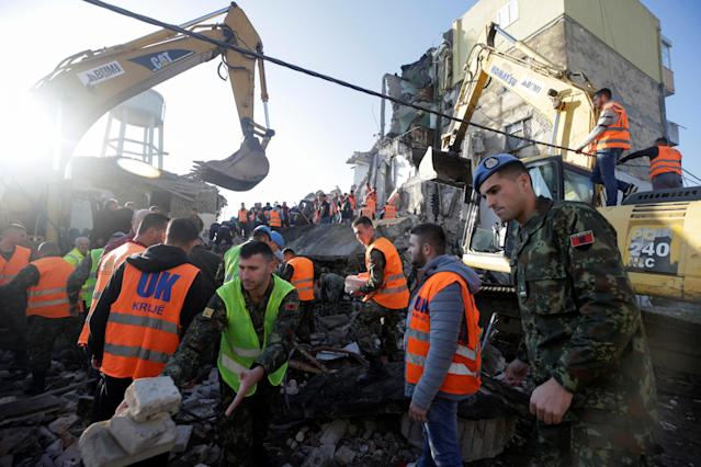 Emergency personnel work near a damaged building in Thumane after an earthquake shook Albania on Nov. 26. (Photo: Florion Goga/Reuters)