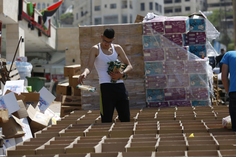 FILE - In this Monday, April 20, 2020 file photo, a man in the West Bank city of Nablus packs boxes with food that will be distributed to poor Palestinian families ahead of the holy month of Ramadan. As Ramadan begins with the new moon later this week, Muslims all around the world are trying to work out how to maintain the many cherished rituals of Islam's holiest month. (AP Photo/Majdi Mohammed, File)