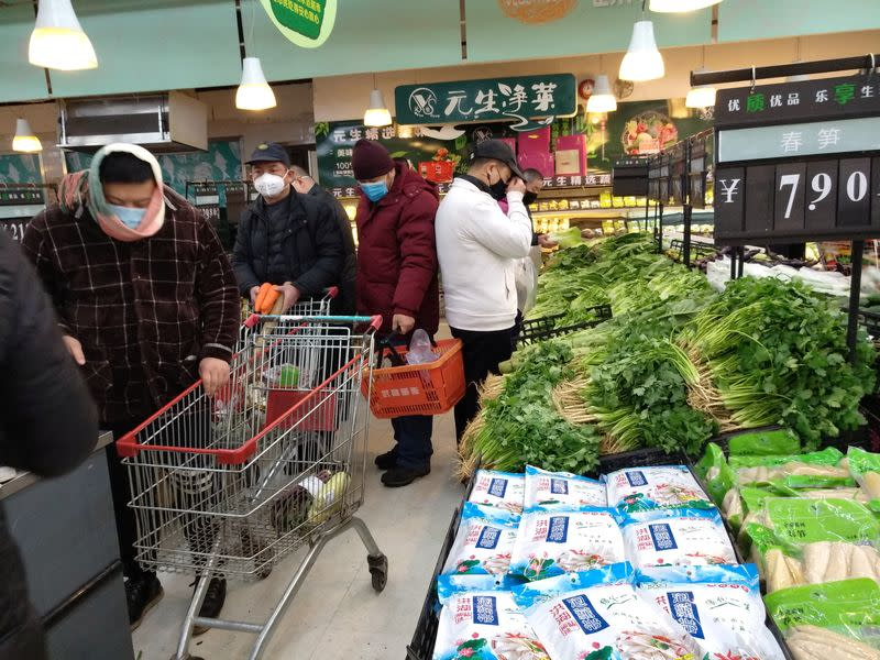 People wearing masks shop at a supermarket on the second day of the Chinese Lunar New Year, following the outbreak of a new coronavirus, in Wuhan, Hubei