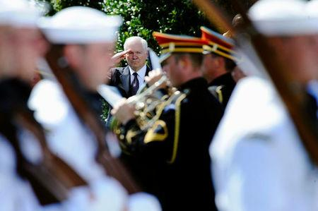 FILE PHOTO: U.S. Defense Secretary Robert Gates (C) salutes as troops perform a march-in-review during his farewell ceremony at the Pentagon in Arlington, Virginia, June 30, 2011. Gates is stepping down after four and a half years as the U.S. defense chief.  REUTERS/Jonathan Ernst/File Photo