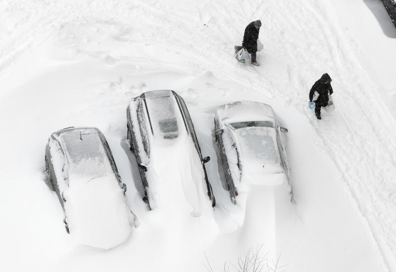People pass by vehicles covered with snow in Kiev, Ukraine, Saturday, March 23, 2013. Heavy snow storms from the Balkan region have been stricken Ukraine since last afternoon, in the last winter attack at the end of the first spring month. (AP Photo/Efrem Lukatsky)