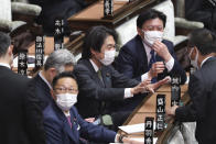 Japanese lawmakers wearing face masks to protect against the spread of the coronavirus attend an ordinary Diet session at the House of Representatives of parliament in Tokyo Monday, Jan. 18, 2021. (AP Photo/Koji Sasahara)