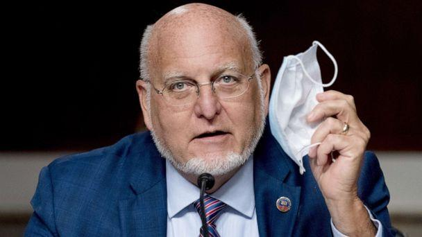 PHOTO: Centers for Disease Control and Prevention Director Dr. Robert Redfield holds up his mask as he speaks at a Senate Appropriations subcommittee hearing on Capitol Hill, in Washington, Sept. 16, 2020. (Andrew Harnik/Pool via Shutterstock)