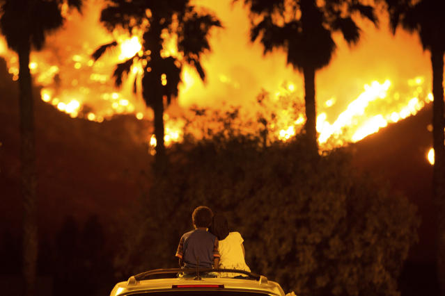 <p>King Bass, 6, left, sits and watches the Holy Fire burn from on top of his parents' car as his sister Princess, 5, rests her head on his shoulder Thursday night, Aug. 9, 2018 in Lake Elsinore, Calif. (Photo: Patrick Record/AP) </p>