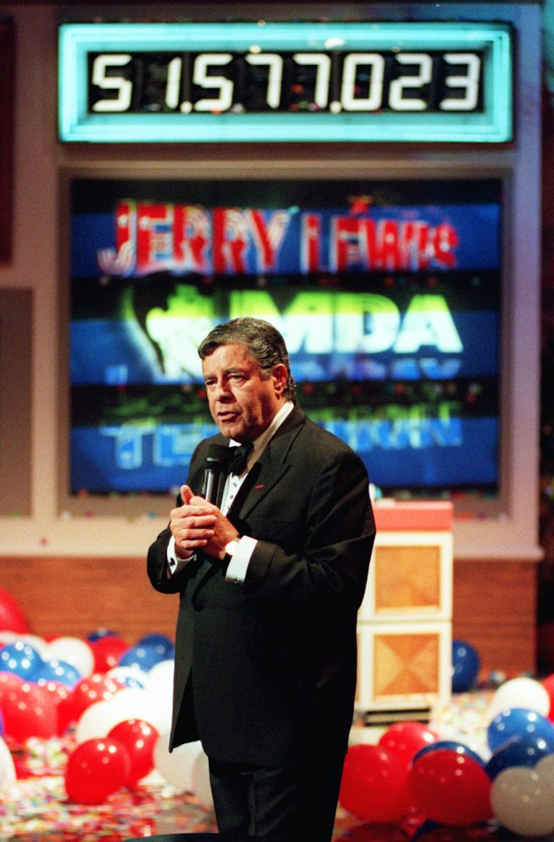 FILE - In this Sept. 7, 1998 file photo, Jerry Lewis stands in front of a countdown board after announcing a record $51.5 million in pledges and contributions for the fight against neuromuscular diseases during, the 33rd annual Jerry Lewis Muscular Dystrophy Telethon in Los Angeles. Labor Day this year promises to be bland by comparison, with the 85-year-old Lewis now banished from the annual rite he built from scratch and molded in his image. (AP Photo/Muscular Dystrophy Association, file)