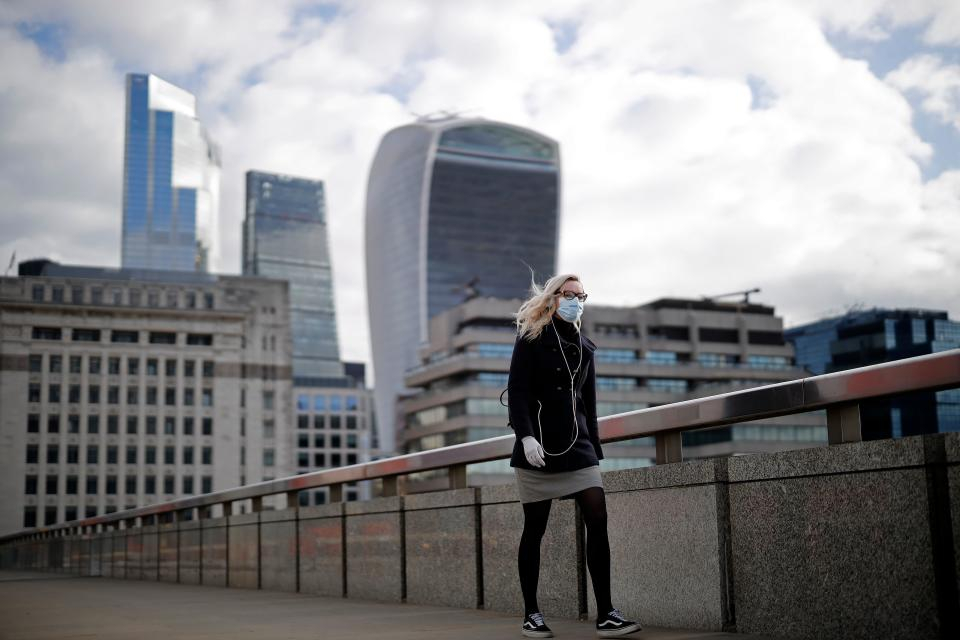 A woman wearing PPE (personal protective equipment), including a face mask as a precautionary measure against COVID-19, walks across London Bridge away from the City of London, in central London on May 13, 2020, as people start to return to work after COVID-19 lockdown restrictions were eased. - Britain's economy shrank two percent in the first three months of the year, rocked by the fallout from the coronavirus pandemic, official data showed Wednesday, with analysts predicting even worse to come. Prime Minister Boris Johnson began this week to relax some of lockdown measures in order to help the economy, despite the rising death toll, but he has also stressed that great caution is needed. (Photo by Tolga Akmen / AFP) (Photo by TOLGA AKMEN/AFP via Getty Images)