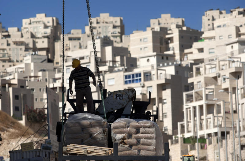 FILE - In this Nov. 2, 2011 file photo, a construction worker works on a new housing unit in the east Jerusalem neighborhood of Har Homa.  Israel is planning its biggest construction surge in east Jerusalem in decades, settlement opponents say, a move that would complicate prospects for restarting peace talks with the Palestinians. With more than 9,000 apartments in the pipeline, Prime Minister Benjamin Netanyahu is reaffirming his opposition to ceding any parts of the holy city to the Palestinians, who say there can be no peace accord without partitioning the holy city.(AP Photo/Sebastian Scheiner, File)