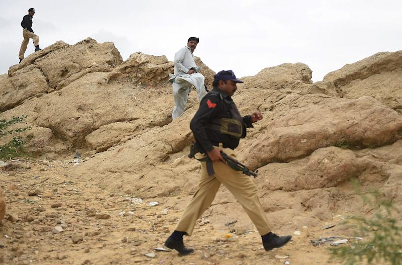 Pakistani policemen take a position at the destroyed hideouts of Taliban militants in the Manghopir area of Karachi on August 21, 2015 (AFP Photo/Rizwan Tabassum)