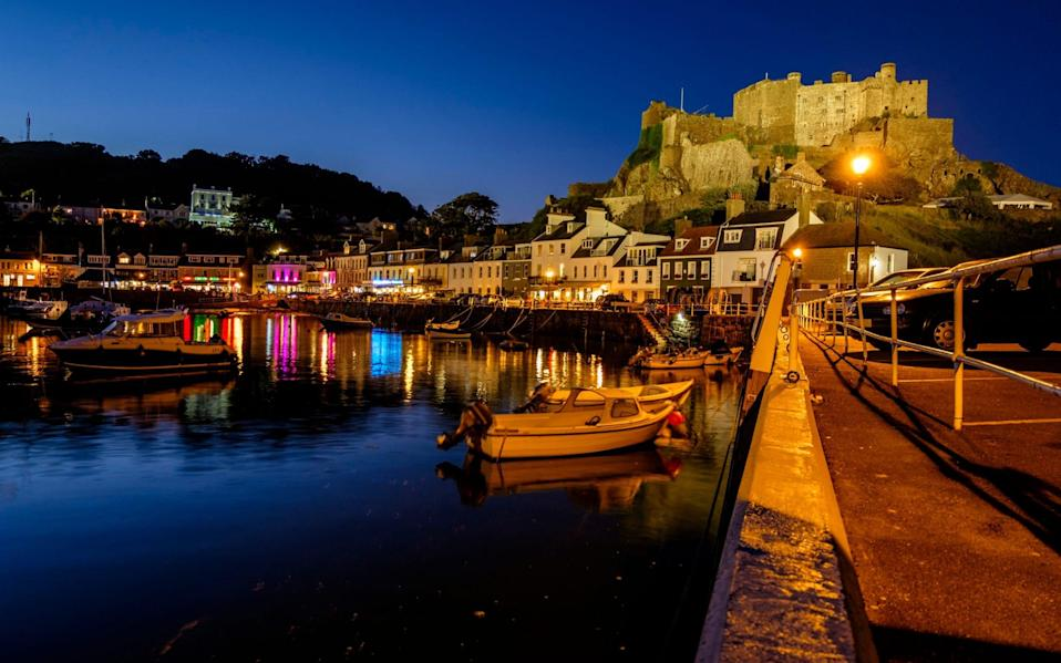 Mont Orgueil Castle, viewed from Gorey Pier at dusk, Gorey, Jersey, Channel Islands - Getty