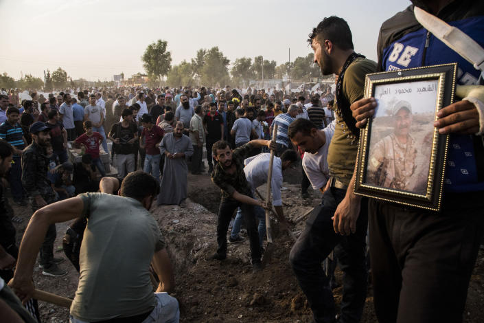 Syrians bury Syrian Democratic Forces fighters killed fighting Turkish advance in the Syrian town of Qamishli, Saturday, Oct. 12, 2019, Turkey's military says it has captured a key Syrian border town Ras al-Ayn under heavy bombardment in its most significant gain as its offensive against Kurdish fighters presses into its fourth day. (AP Photo/Baderkhan Ahmad)