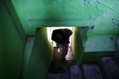 Ambreen Hannan, comes out of the underground shelter, build to hide from the shelling, at her home in Chakothi in Kashmir