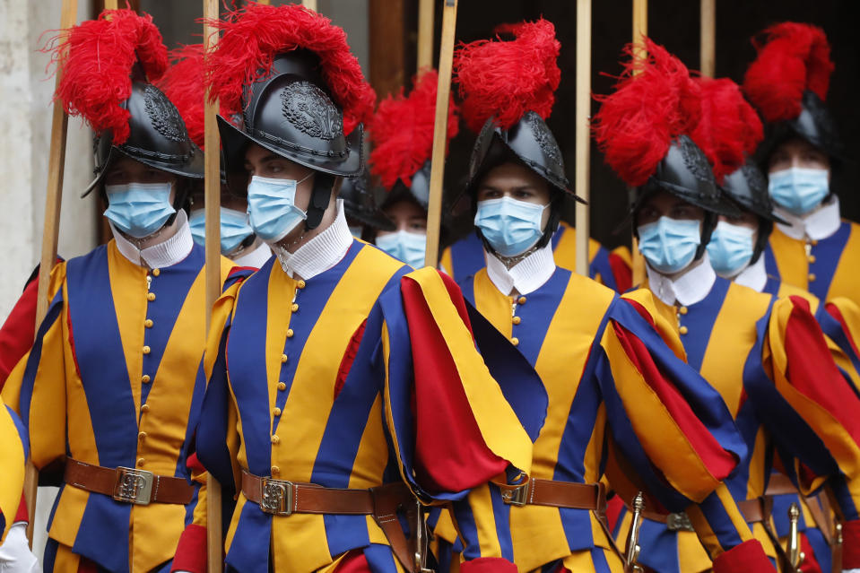 Vatican Swiss Guards, wearing masks to curb the spread of COVID-19, leave the St. Damaso courtyard after Spain's Prime Minister Pedro Sanchez meeting with Pope Francis, at the Vatican, Saturday, Oct. 24, 2020. (AP Photo/Alessandra Tarantino)