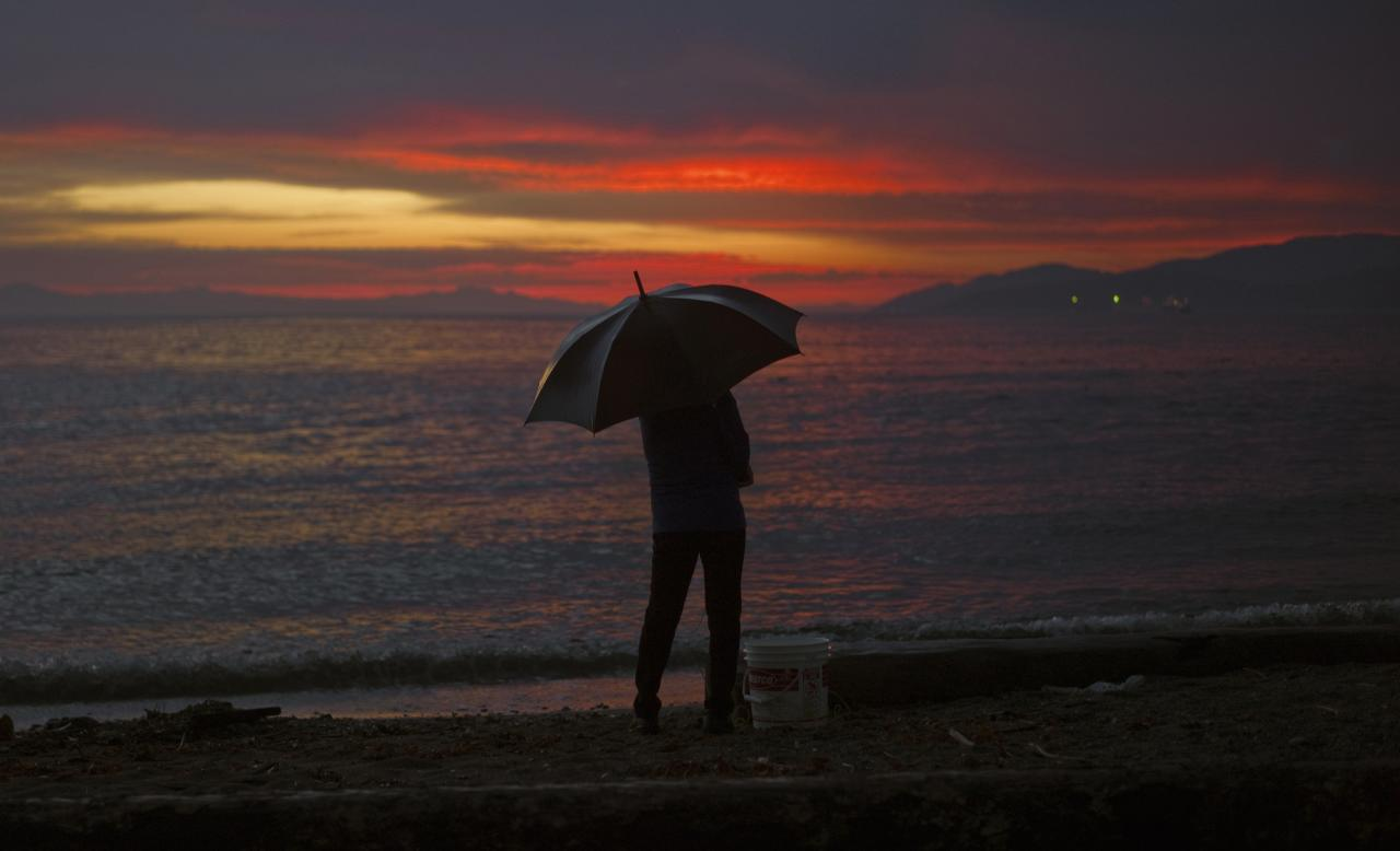 A woman stands in the rain at sunset along the shoreline in West Vancouver, British Columbia September 5, 2013. REUTERS/Andy Clark (CANADA - Tags: SOCIETY TPX IMAGES OF THE DAY ENVIRONMENT)