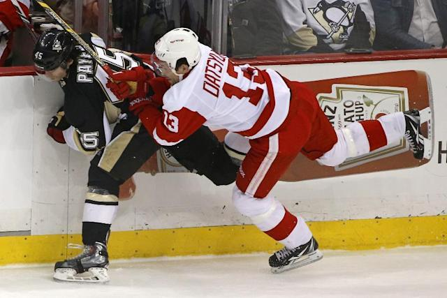 Detroit Red Wings' Pavel Datsyuk (13) collides with Pittsburgh Penguins' Adam Payerl (45) along the boards during the first period of an NHL hockey game in Pittsburgh, Wednesday, April 9, 2014. (AP Photo/Gene J. Puskar)