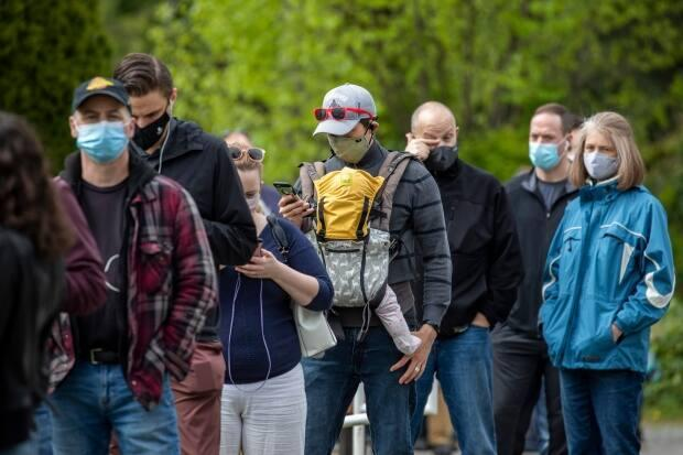 People are pictured lined up to receive their COVID-19 vaccine during a walk-in clinic at the Poirier Forum in Coquitlam, British Columbia on Tuesday, April 27, 2021.  (Ben Nelms/CBC - image credit)