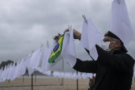 """An activist hangs a Brazilian flag on a clothesline on Copacabana beach amid white scarves that represent people who have died of COVID-19 in Rio de Janeiro, Brazil, Friday, Oct. 8, 2021. The action was organized by the NGO """"Rio de Paz"""" to protest the government's handling of the pandemic as the country nears a total of 600,000 COVID-19 related deaths. (AP Photo/Bruna Prado)"""