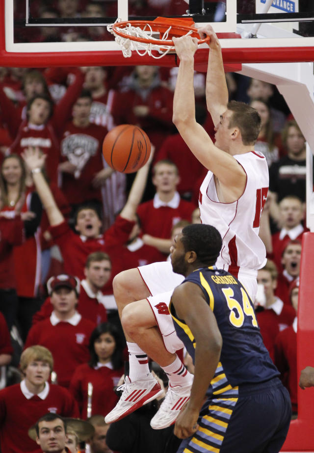 Wisconsin's Sam Dekker, top, dunks over Marquette's Davante Gartner during the first half of an NCAA college basketball game Saturday, Dec. 7, 2013, in Madison, Wis. (AP Photo/Andy Manis)