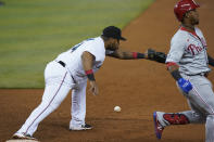 Miami Marlins first baseman Jesus Aguilar, left, is unable to catch the throw as Philadelphia Phillies' Jean Segura reaches first during the third inning of a baseball game, Monday, May 24, 2021, in Miami. (AP Photo/Wilfredo Lee)