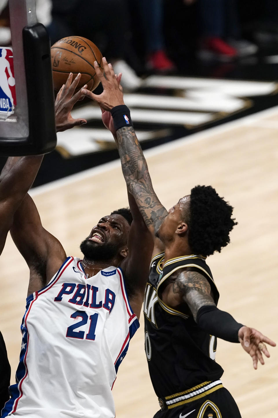 Philadelphia 76ers center Joel Embiid (21) battles Atlanta Hawks forward John Collins, right, as he goes up for a basket during the first half of Game 6 of an NBA basketball Eastern Conference semifinal series Friday, June 18, 2021, in Atlanta. (AP Photo/John Bazemore)