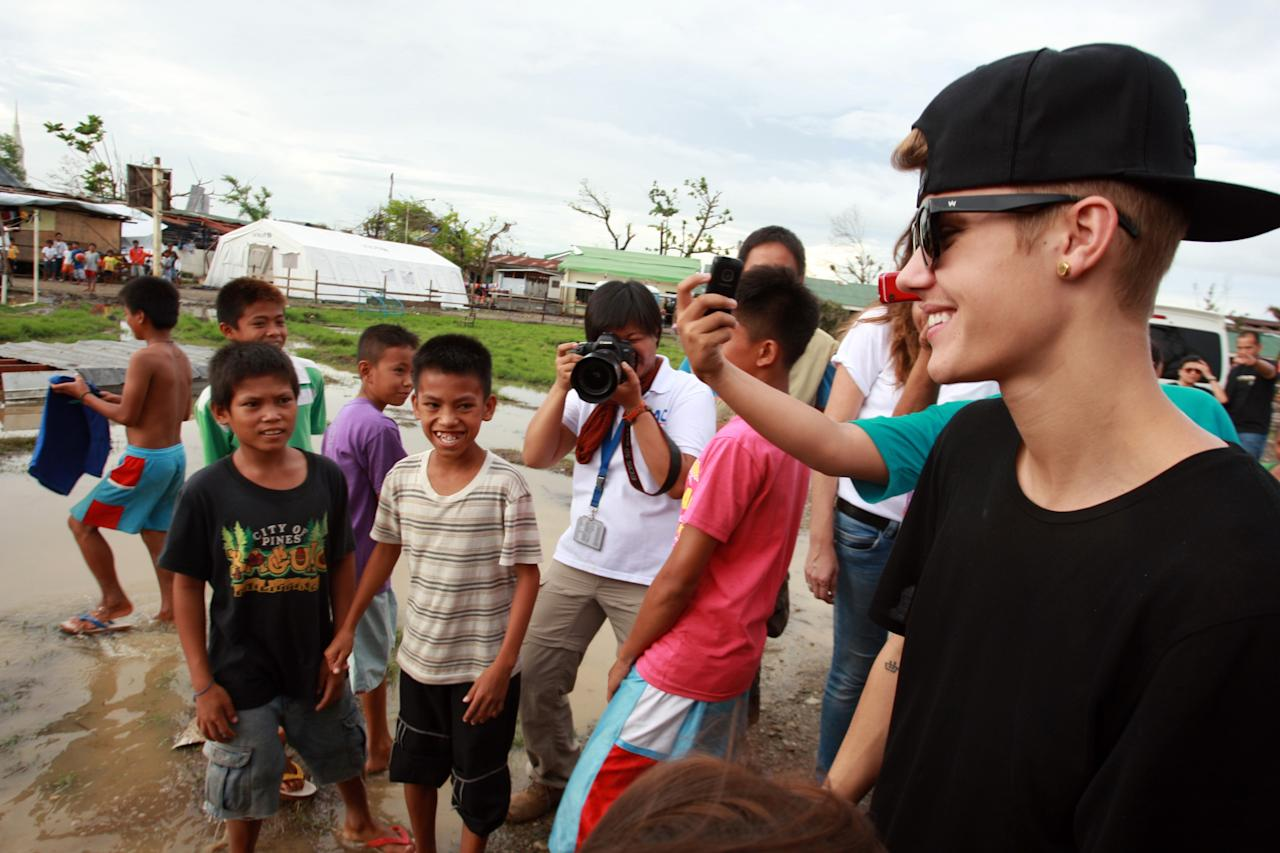 TACLOBAN, LEYTE, PHILIPPINES - DECEMBER 10: Children look to Justin Bieber as he visits San Jose Elementary School on December 10, 2013 in Tacloban, Leyte, Philippines. Bieber previously launched a campaign to help raise money for the victims of super Typhoon Haiyan. Typhoon Haiyan which ripped through Philippines over a month ago has been described as one of the most powerful typhoons ever to hit land, leaving thousands dead and hundreds of thousands homeless. Countries all over the world have pledged relief aid to help support those affected by the typhoon as the relief effort continues. (Photo by Jeoffrey Maitem/Getty Images)
