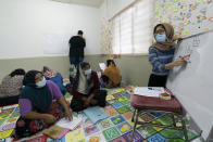 A volunteer teacher, right, gives a basic English lesson to a minority Muslim Rohingya refugees at a slum on the outskirts of Kuala Lumpur, Malaysia, on Oct. 11, 2020. Refugee women in Malaysia, some in their late 50s, are learning to read and write for the first time. The classes outside Kuala Lumpur are offered by the Women for Refugees group, which was formed in September by two law students to help illiterate migrant women integrate into the local community and empower them to be more than just passive wives. (AP Photo/Vincent Thian)