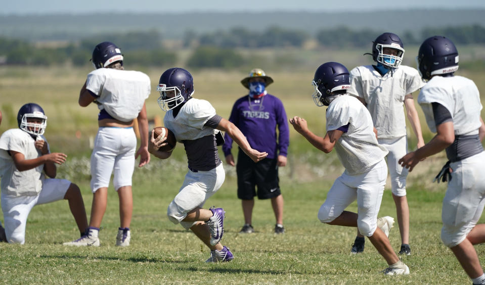 Thrall High School football players, wearing face masks at all times and using social distancing when possible, go through a practice, Thursday, Aug. 13, 2020, in Thrall, Texas. Coronavirus testing in Texas has dropped significantly, mirroring nationwide trends, just as schools reopen and football teams charge ahead with plans to play. (AP Photo/Eric Gay)