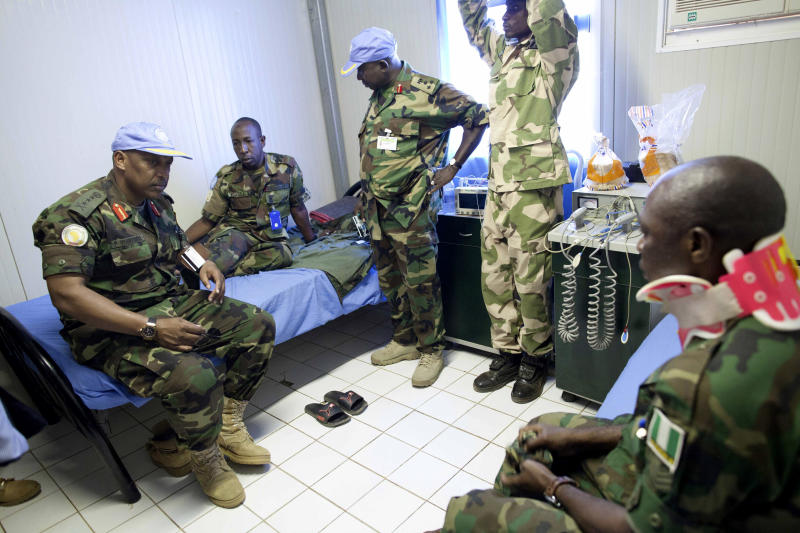 """In this photo released by the United Nations African Mission in Darfur (UNAMID), UNAMID Force Commander, Lieutenant General Patrick Nyamvumba from Rwanda, left, talks to an injured peacekeeper after an ambush Tuesday night that killed four peacekeepers, in El Geneina, Sudan, Wednesday, Oct. 3, 2012. United Nations spokesman Martin Nesirky says the secretary-general """"is appalled and deeply saddened"""" at an attack that killed four Nigerian peacekeepers and wounded eight in Sudan's restive West Darfur region. (AP Photo/Albert González Farran, UNAMID)"""